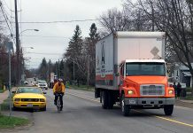 A cyclist passes a parked car on River Road in Peterborough, while the driver of a truck gives ample space when passing the cyclist. Giving a minimum of one metre of space when passing a cyclist is the law. The one-metre cushion is designed to keep everyone safe on our roads. (Photo: Lindsay Stroud)