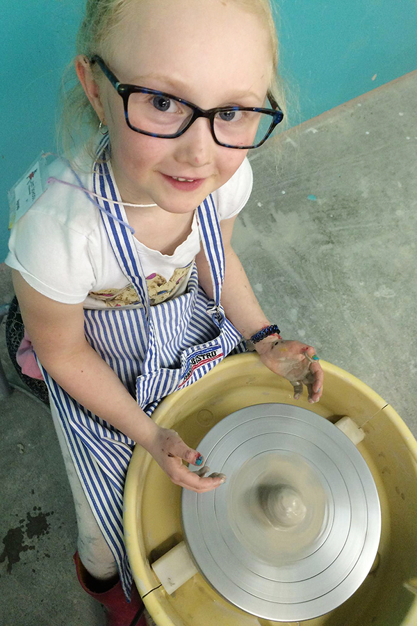 Using a potter's wheel is one of the camper's favourite experiences, where they get their hands dirty by forming, shaping and molding soft clay. (Photo: Art School of Peterborough)