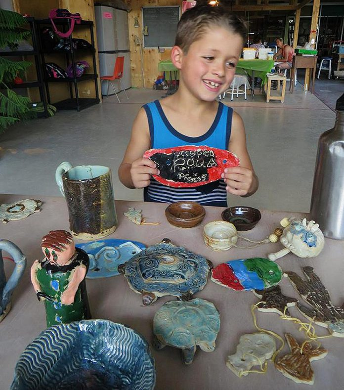 A camper poses with an art project he created at camp. Every day, campers will spend some or all of the day creating with clay, guided step-by-step by qualified instructors through the process. (Photo:  Kawartha Potters' Guild)