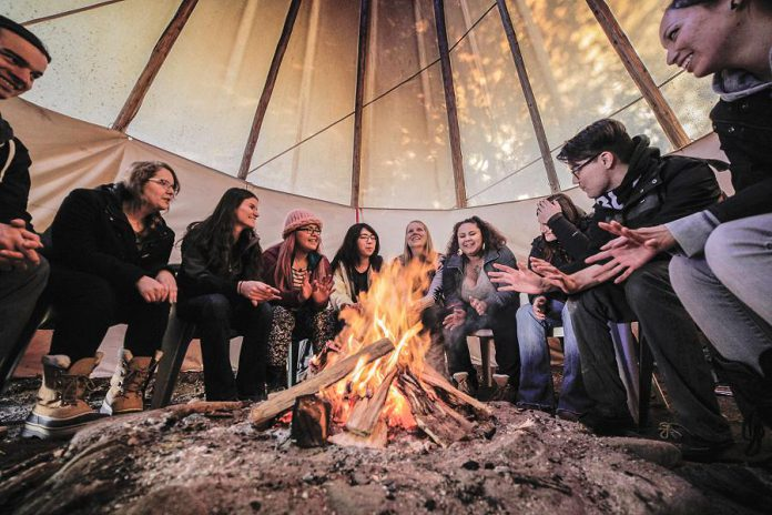 Students sit in a tipi on Symons Campus at Trent University as they listen to a professor. Trent University has consolidated and renamed its indigenous studies program as the Chanie Wenjack School for Indigenous Studies, in honour of the nine-year-old Anishinaabe boy who died from exposure when trying to get home after running away from a residential school in Kenora in 1966. (Photo: Trent University)