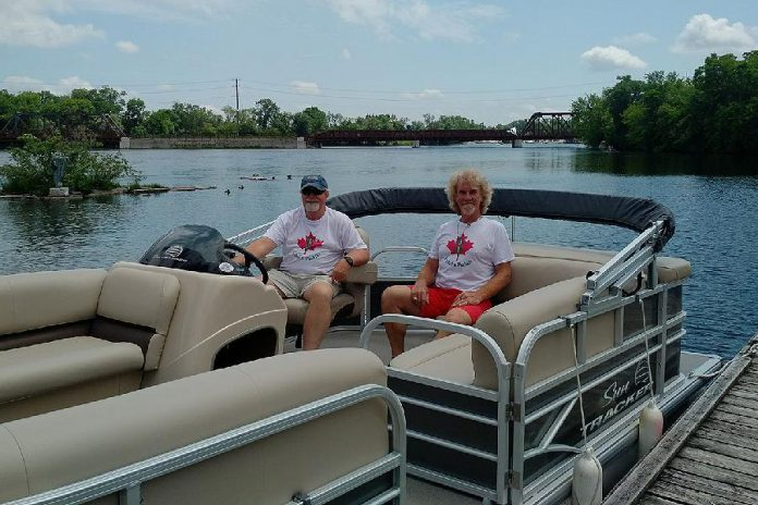 Moe Grant and Lloyd Graham of Pedal 'n' Paddle in the pontoon boat they've added to their fleet of canoe, kayak, bicycle, and pedal boat rentals at The Boat House at Millennium Park.