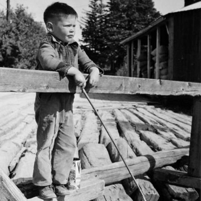 Five-year-old Neil Young in August 1950, fishing from a wooden bridge over the Pigeon River in Omemee. (Photo: Harold Whyte)