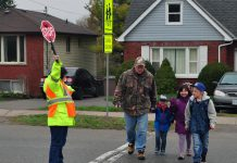 A group walks safely at a school crossing with the help of a City of Peterborough crossing guard. Walking to school is a great way for kids to have a little fun and make connections with neighbours and friends. The Crossing Guards of Peterborough would like to remind drivers to slow down when approaching a school-crossing zone to ensure everyone's safety. (Photo: GreenUP)