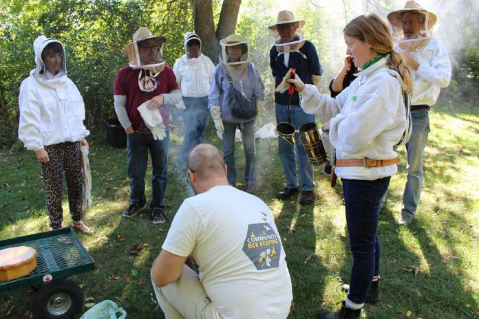 GreenUP's Resident Beekeeper Marcy Adzich shows a group of community members how a hive smoker works at an Open Hive! event at GreenUP Ecology Park in Peterborough while a member of the GreenUP Community Beekeeping Program assists with the demonstration. The hive is smoked so that the bees will not sting when the group enters the hive. (Photo: Karen Halley)