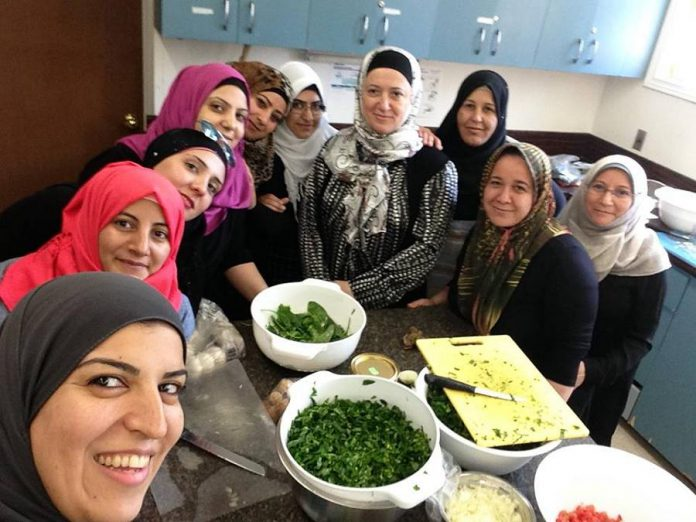 Reem, Fatma, Wesal, Hayfa, Ramya, Enas, Jommana, Dilshah, Ameena and Rafa make Syrian dishes through Newcomer Kitchen, a program led by the New Canadians Centre and hosted in the kitchen of the Beth Israel Synagogue. (Photo: Newcomer Kitchen)