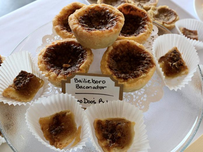 On Saturday, September 23rd, local tart makers will face off in the fifth annual Butter Tart Tour Taste-Off in Peterborough. Pictured is the Bailieboro Baconator, a bacon-enhanced butter tart by Diane Rogers of Doo Doo's bakery. (Photo: Eva Fisher / kawarthaNOW)