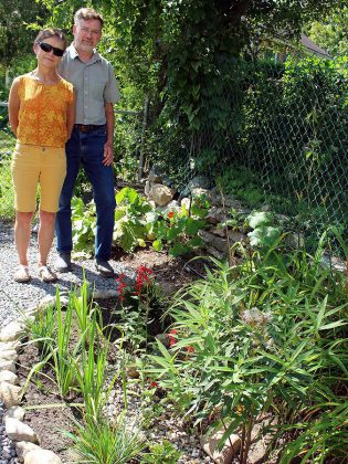 Peterborough residents David Marshall and Barbara Moffat next to a rain garden they installed in their back yard after being inspired by a GreenUP Ready For Rain Workshop. They have transformed their entire property by installing many water-wise features including rain barrels, a smart irrigation system, and by de-lawning the entire property to replace grass with native plants and wildflowers. (Photo courtesy of GreenUP)