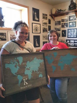 "Workshop participants show their designs from the workshop at the Black Horse Pub. There are a multitude of options, ranging from family surname signs with the option for an ""established"" date to a world map to sayings from poems and songs. (Photo: Anchor & Co.)"