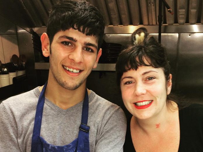17-year-old Omar Hattab, a new Canadian from Syria, with Sue Houde, who owns and operates Two Dishes restaurant in downtown Peterborough along with her sister Paula. Omar is now working at Two Dishes doing what he loves, baking, thanks to Sue and Paula with support from the New Canadians Centre. (Photo courtesy of New Canadians Centre)