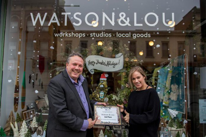 Erin Watson, co-owner of Watson & Lou, receives her second place award in the annual Holiday Window Contest from DBIA Executive Director Terry Guiel. (Photo: Peterborough DBIA)