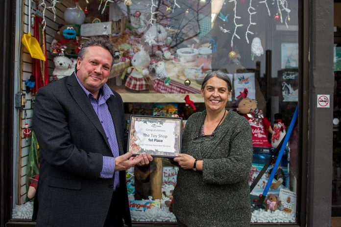 Peterborough DBIA Executive Director Terry Guiel presents The Toy Shop owner Jean Grant with her first place prize in the annual Holiday Window Contest, which was judged by little brothers and sisters from Big Brothers Big Sisters of Peterborough. Grant is donating her $300 prize to the Salvation Army Toy Drive. (Photo: Peterborough DBIA)