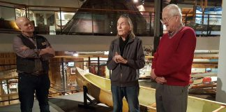 Gordon Lightfoot speaks at The Canadian Canoe Museum as museum curator Jeremy Ward (left) and Lightfoot's friend and fellow canoest Fred Gaskin looks on. The yellow canoe behind Lightfoot is one of three canoes he is donating to The Canadian Canoe Museum collection, along with one canoe donated by Gaskin. (Photo: Jeannine Taylor / kawarthaNOW.com)