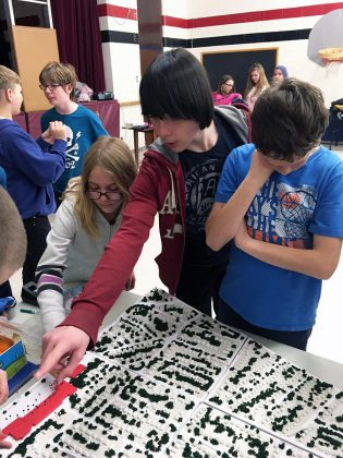 Grade 7 and 8 students at Highland Heights Public School share stories about their neighbourhood during a NeighbourPLAN Map Chat event at their school. Here, students point out areas of interest on a 3D model of their neighbourhood and share ideas about what works and where improvements could be made. (Photo: GreenUP)