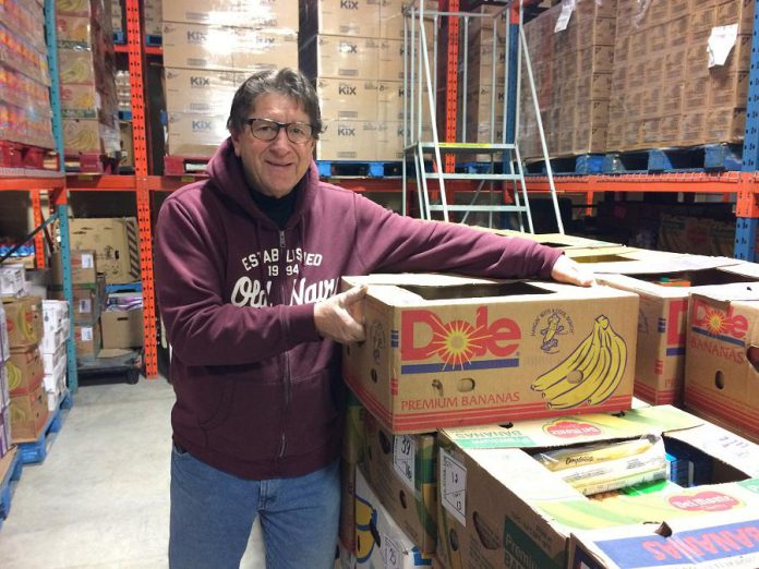 Dave Ralph, Chair of the Kawartha Food Share, stacks boxes of sorted food for families throughout the Kawarthas. (Photo: Eva Fisher / kawarthaNOW.com)