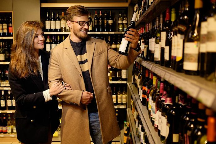 Couple buying a bottle of wine in a liquor store
