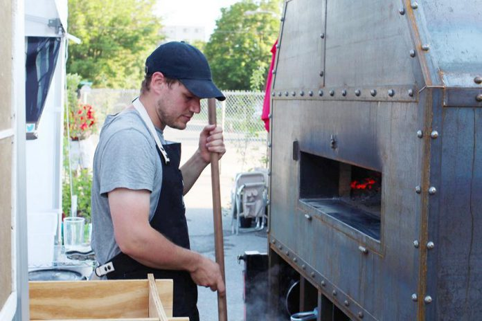 Hard Winter Bread Company co-owner Graham Thoem with the bakery's custom-made wood-fired bagel oven, which is mobile so they can take it to local farmers' markets and bake fresh bagels on site.  (Photo courtesy Hard Winter Bread Company)