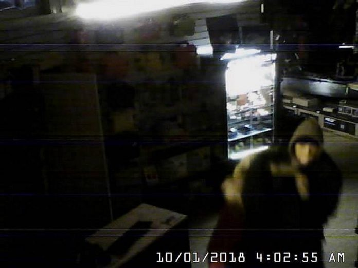 One of the thieves captured on a security camera inside the store with one of the parkas. (Photo: Wild Rock / Facebook)