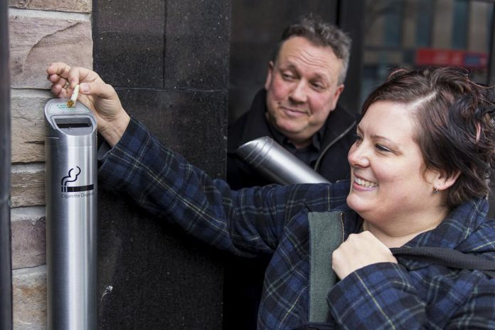 Volunteer Donna Reid, who also coordinates the annual Butt Blitz in Peterborough, disposes of a cigarette butt in one of the new receptacles in downtown Peterborough as DBIA Executive Director Terry Guiel looks on. The DBIA is offering the free receptacles to its members. (Photo: Peterborough DBIA)