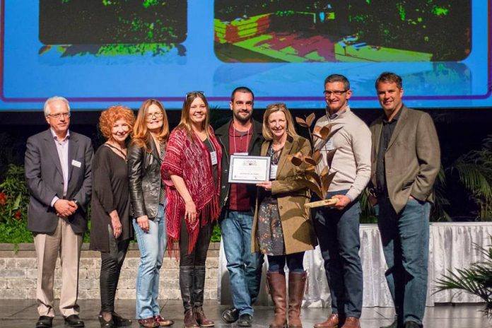 "Robin Burrows, owner of Gilstorf & Gray of Bobcaygeon (fourth from left), with lead designer Julie Moore of Modern Landscape Designers (holding the plaque) and other team members accepting the ""Tony Di Giovanni Award – Judges Choice Garden of the Year 2018"" from Canada Blooms officials. (Photo: Modern Landscape Designers)"