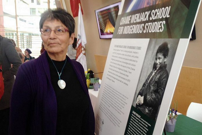 Pearl Achneepineskum, one of Chanie Wenjack's sisters, in front of a photo of her brother. (Photo: Paul Rellinger / kawarthaNOW.com)