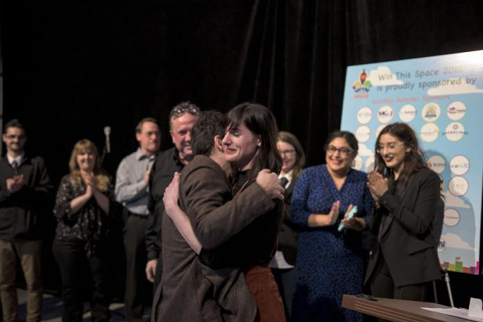 Nadine McCallen receives a hug after winning the 2018 Win This Space entrepreneurial competition at The Venue in downtown Peterborough on March 1, 2018. McCallen receives a grand prize package valued at more than $45,000 that includes a free year-long lease for a downtown Peterborough storefront. (Photo courtesy of Peterborough DBIA)