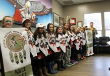 Players from the Curve Lake First Nation Nimkiins Kwe Novice Girls and Atom Girls teams display their championship banners to Chief and Council: Danika Jacobs, Maggie Jevons, Sierra Jacobs, Miley Garbutt, Naomi Coppaway, McKenzie Taylor, Goldie Whetung, Brittany Foster, Abigail Jacobs, Kenzie McIntyre, Marissa Williams, and Chief Phyllis Williams. (Photo courtesy of Curve Lake First Nation)