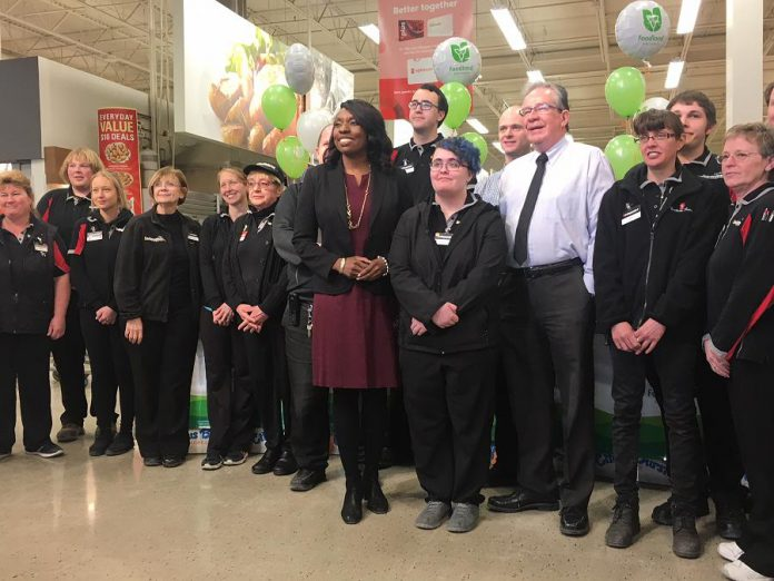 Morello's Independent Grocer employee Amanda Gurney, who spoke about the job opportunity provided her through Employment Planning and Counselling, joins MPPs Jeff Leal and Mitzie Hunter and some of the store staff gathered for Tuesday's Employing Young Talent Incentive announcement. (Photo: Paul Rellinger / kawarthaNOW.com)
