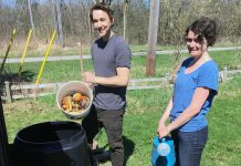 "Connor Overbaugh, Summer Waste Technician with the City of Peterborough, helps Peterborough resident Jenn McCallum install a composter as part of the new partnership program with GreenUP called ""Kitchen to Compost: Too Good To Waste"". Peterborough residents can sign up to have a composter delivered and installed for $20. (Photo courtesy of GreenUP)"