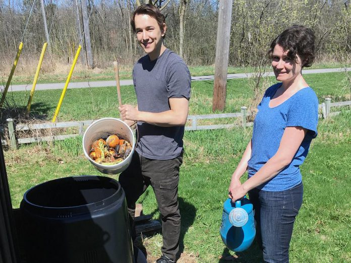 """Connor Overbaugh, Summer Waste Technician with the City of Peterborough, helps Peterborough resident Jenn McCallum install a composter as part of the new partnership program with GreenUP called """"Kitchen to Compost: Too Good To Waste"""". Peterborough residents can sign up to have a composter delivered and installed for $20. (Photo courtesy of GreenUP)"""