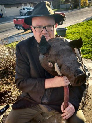 kawarthaNOW's theatre reviewer Sam Tweedle poses with the pig's head, one of the props from the production.