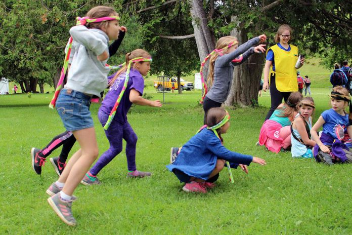 Attendees of this year's Peterborough Children's Water Festival participate in the Sponge Bog Frog activity centre, led by a high school volunteer, seen in the yellow apron. For this activity, students are frogs who need to hop safely from their hibernation spot to their pond after experiencing both positive and negative events (pollution, garbage, chemicals) along the way. (Photo: Karen Halley / GreenUP)