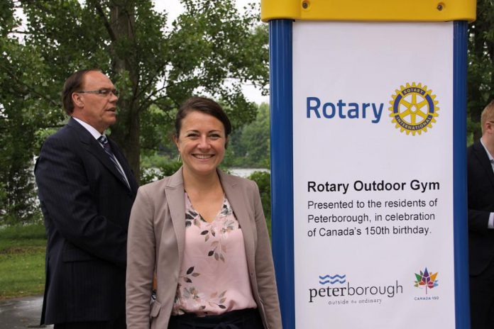 City councillor and mayoral candidate Diane Therrien stands beside the Rotary Outdoor Gym sign. Sevearl years in the making, the project was announced in 2017 as part of Canada's 150th birthday. Peterborough Mayor Daryl Bennett, who also made remarks at the opening, is pictured in the background. (Photo: Jeannine Taylor / kawarthaNOW.com)