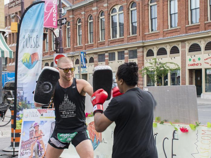 Mike Doherty and Nathanial Kumarasamy of Dohjo Muay Thai show off their skills at the corner of Charlotte and George streets during the June 20th media launch for this year's Peterborough Pulse. The one-day event on July 21st will feature a range of activities, art and music, food, and more. (Photo courtesy of Peterborough Downtown Business Improvement Area)
