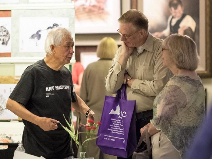 Artist Charles Leung, an alumni exhibitor with the Buckhorn Fine Art Festival, chats with attendees at the Buckhorn Fine Art Festival. (Photo courtesy of Buckhorn Fine Art Festival)