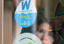 GreenUP Water Programs Coordinator Jenn McCallum places a BlueW Ptbo decal in the window at Black Honey Café on Hunter Street in downtown Peterborough. Look for the decal across the Kawarthas at businesses and public service buildings, marking them as destinations for re-filling up your reusable water bottle for free, or check bluewptbo.ca for a full listing. (Photo: Karen Halley / GreenUP)