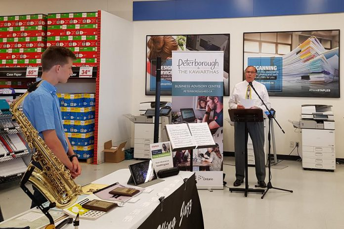 Peterborough Mayor Daryl Bennett speaks at the Summer Company-Staples Youth Entrepreneurship Day on July 4, 2018 at Staples in Peterborough, as young entrepreneur Noah Abrahamse of GoldWing Jazz looks on. (Photo: Amy Bowen / kawarthaNOW.com)