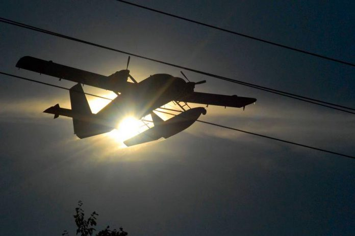 The De Havilland DHC-6-300 Twin Otter water bomber silhouetted against the sun.  (Photo courtesy of Dean Nighswander)