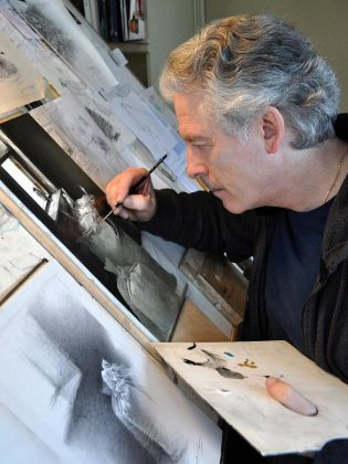 "Famed Canadian wildlife artist Michael Dumas, one of the founding members of the Buckhorn Fine Art Festival, at work on ""Looking Out"". The original graphite study is the featured painting in ""The Lives of Birds"" and is one of two prize draws on opening night on Friday, August 17. (Photo courtesy of Buckhorn Fine Art Festival)"