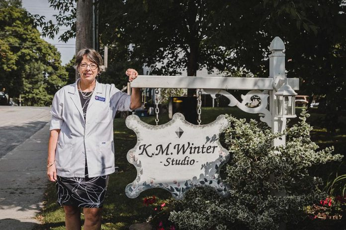 Kim Winter in front of her home-based studio in Peterborough. K.M. Winter Jewellery Studio supplies custom design and remodeling in gold, silver and platinum, engagement and wedding rings, jewellery appraisals and insurance replacement, jewellery repairs and lapidary, diamonds, colour stones, pearls, and opals. (Photo: Heather Doughty)