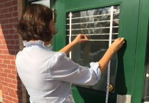 Many millions of birds in Canada die each year from collisions with windows. Ewa Bednarczuk, Ecology & Stewardship Specialist with Lower Trent Conservation, applies small white adhesive markers to window glass on a door. The markers are spaced to provide a visual cue to birds that the window is not open space. (Photo courtesy of Lower Trent Conservation)