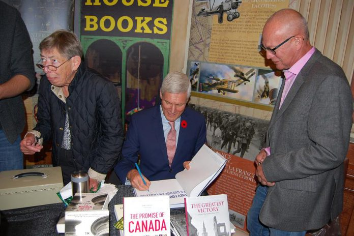"Historian and playwright Hugh Brewster, who wrote the play ""Last Day, Last Hour - Canada's Great War on Trial"" which will be performed during Armistice 18, signs a book during the opening ceremony on Sunday, September 30, 2018. (Photo: April Potter / kawarthaNOW.com)"
