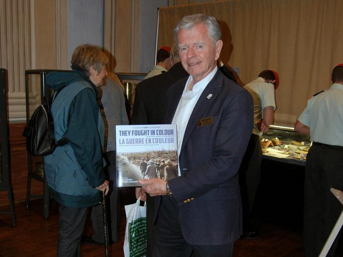 "Port Hope Mayor Bob Sanderson at the opening ceremony of Armistice 18 on Sunday, September 30, 2018, with a copy of ""They Fought In Colour"", a new photographic exploration from The Vimy Foundation of Canada's First World War experience presented for the first time in full, vibrant colour, with commentary from some of Canada's leading public figures,  including Paul Gross, Peter Mansbridge, Margaret Atwood, Tim Cook, and many others. (Photo: April Potter / kawarthaNOW.com)"