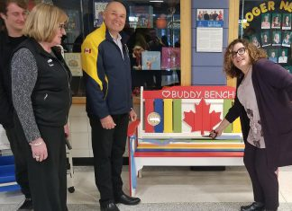 Roger Neilson Public School principal Denise Humphries (right) cuts the ribbon on the Rotary Buddy Bench as Nate Loch, Rotarian Donna Geary, and Rotary Club of Peterborough president Brian Prentice look on. Geary and her son Nate initiated the Rotary Buddy Bench program in Peterborough last year, donating a bench to St. Catherine's Catholic Elementary School in Peterborough. (Photo: Rotary Club of Peterborough Kawartha)