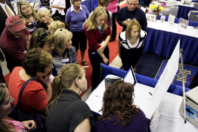 People gather around a display at Love Local Expo, the region's largest business trade show, in 2016. For the first time ever, this year's Love Local Expo takes place at the Evinrude Centre in Peterborough. Featuring more than 90 local businesses, Love Local Expo runs from noon to 7 p.m. on Wednesday, October 3, 2018. The event is free, there's lots of free parking, and there will be prizes including a notebook computer. (Photo: Peterborough Chamber of Commerce)