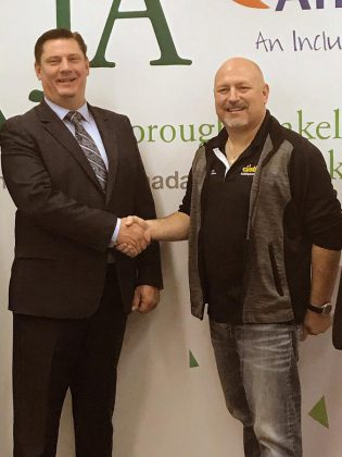 Michael Skinner, chancellor of the 2019 Junior Achievement of Peterborough Lakeland Muskoka Business Hall of Fame, thanks Brent Perry, president of Alf Curtis Home Improvements Inc., for the investment of $15,000. (Photo courtesy of JA-PLM)