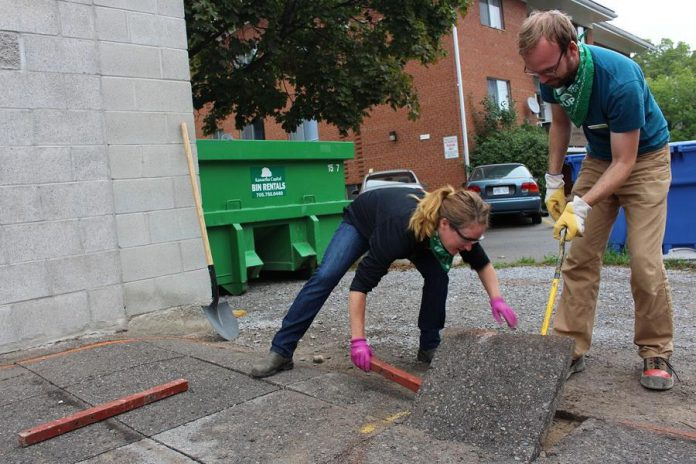 Volunteers remove pavement at the corner of Brock St. and Park St. in Peterborough, where a busy walkway in front of The Wine Shoppe on Park was transformed in 2016 from asphalt into a beautiful garden to divert 200 cubic meters of stormwater. GreenUP's fourth and largest Depave Paradise project will take place at the new Downtown Vibrancy Project site at the south end of Millennium Park, behind the No Frills parking lot, on October 11 and 12, 2018. (Photo: GreenUP)