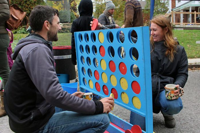 Two attendees of the Sophia Street Pulse Pop-up play giant board games that were set up on the street by Boardwalk Game Lounge, who will soon be opening soon in downtown Peterborough. (Photo: Karen Halley)