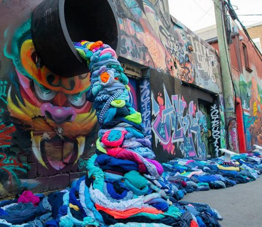 """It takes 2,650 litres of water to produce a single cotton t-shirt, and Canadians throw away more than 12 million tonnes of clothing and textiles every year, 95 per cent of which could be reused or recycled. Pictured is part of an interactive art installation about textile waste in Graffiti Alley of Toronto's Fashion District created by Value Village Thift Store for """"Textile Tuesday"""" during Waste Reduction Week, which takes place until October 21st. (Photo: Value Village / Instagram)"""