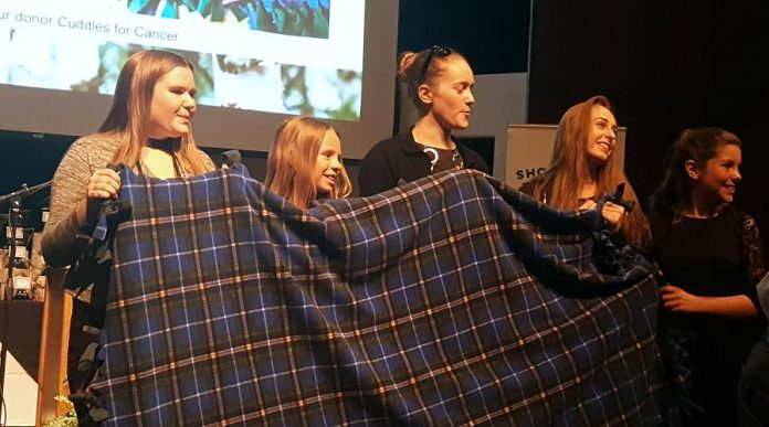 During the live auction, members of the new youth council of Cuddles for Cancer react with delight to a $1,000 bid from Roberta Herod for the 4,000th blanket created by founder Faith Dickinson. (Photo: Jeannine Taylor / kawarthaNOW.com)