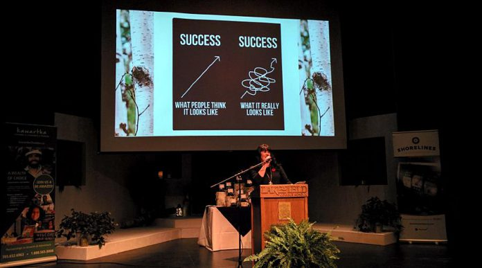 Emcee Cindy Windover, who later would receive the Citizen of the Year award, entertains the crowd with a slide demonstrating the perception versus the reality of achieving success in small business. (Photo: Bruce Head / kawarthaNOW.com)